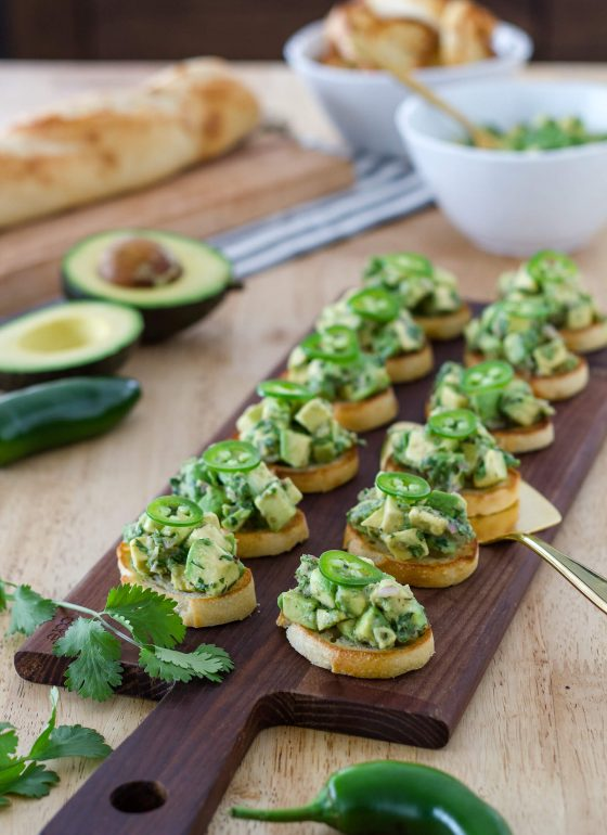 Delicious bruschetta topped with an aromatic mixture of avocados, herbs, garlic, and jalapenos. They are easy to make and perfect for a snack, appetizer, or tapas dinner. Recipe at www.designsofanykind.com