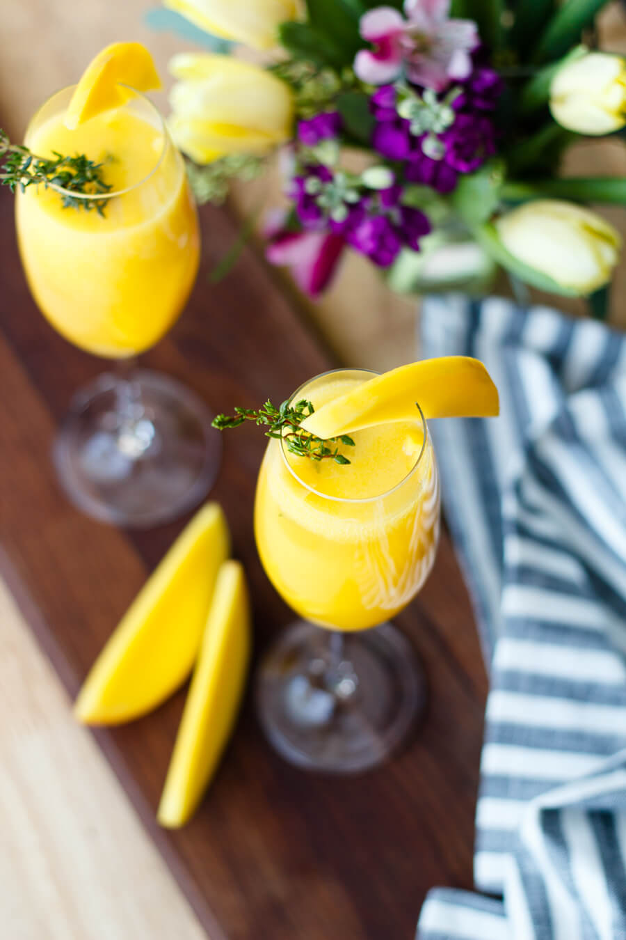 Pop open a bottle of champagne and celebrate the spring season with these mango thyme mimosas that are as beautiful as they are delicious! Recipe at www.designsofanykind.com