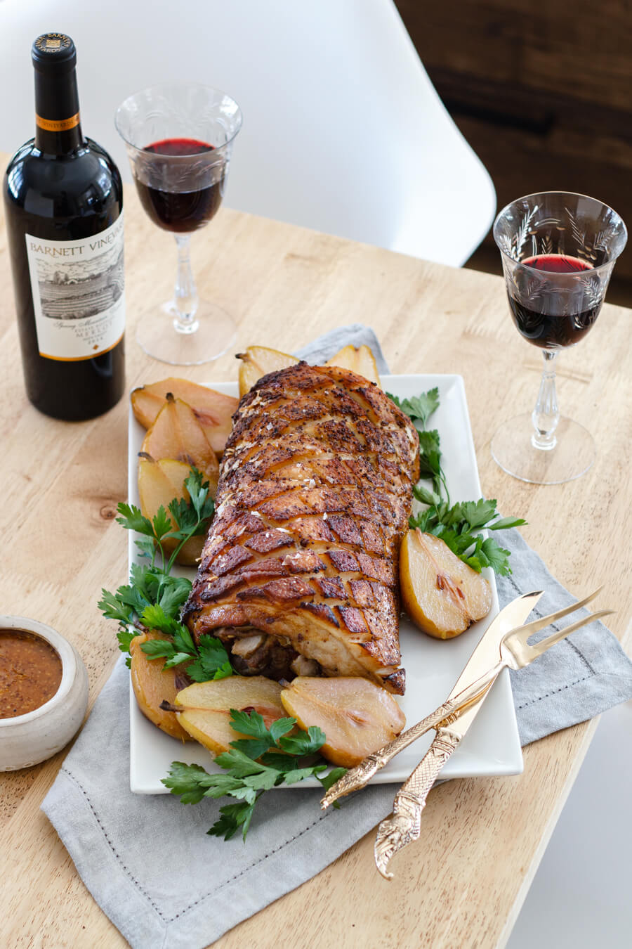 Make this tender, slow roasted pork belly marinated in bourbon mustard and stuffed with tangy pears. A stunning dish for your next dinner party. Recipe at www.designsofanykind.com.