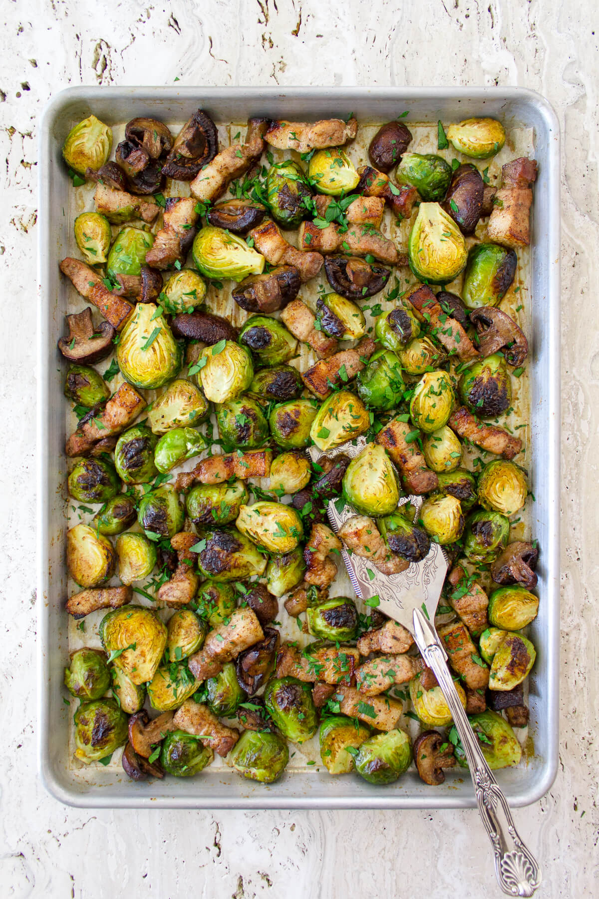 These Roasted Brussel Sprouts with Pork Belly & Mushrooms are super easy to make and roast in one pan for a very delicious side dish! Recipe at www.designsofanykind.com